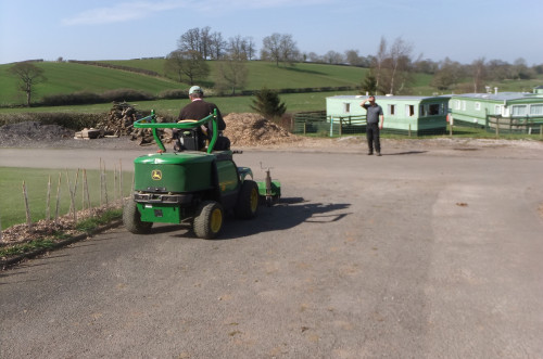 Sweeping road on caravan site with a John Deere F1435 and Kersten KM 15045 front mounted sweeper